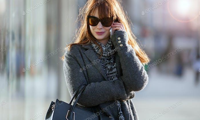 Chica en la calle usando el teléfono móvil
