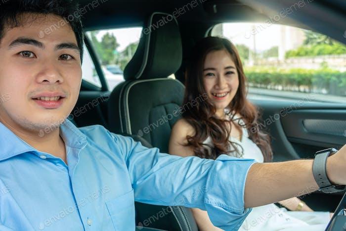 Азиатская пара едет в машине для тест-драйва, прежде чем купить новый автомобиль,