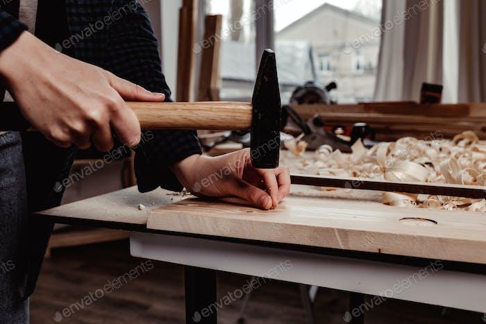 Human hands hammer nail into a wooden bar