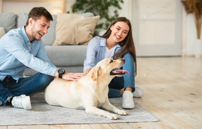 Young family of two sitting on floor with dog