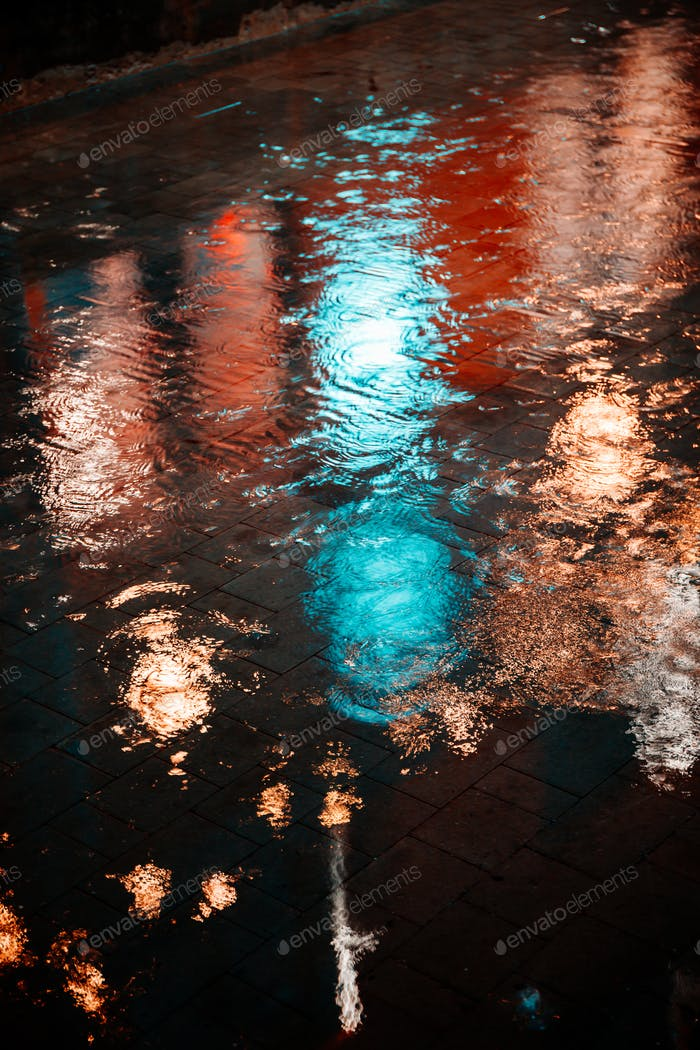 Raindrops on asphalt in the light of evening lights