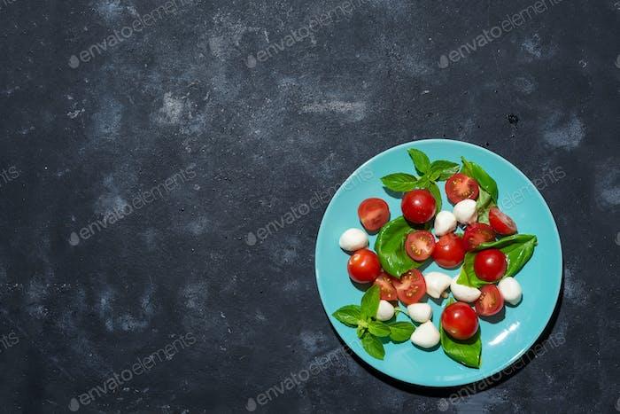 Fresh italian caprese salad with mozzarella and tomatoes on blue plate