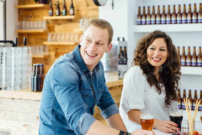 Man and woman smiling at table with beer