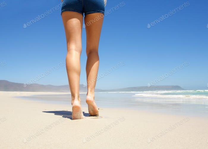 Legs walking barefoot on beach