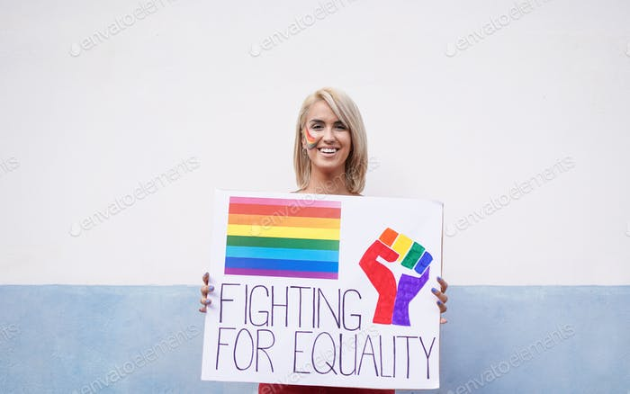 Happy young woman at gay pride event with fighting for equality banner - Concept of LGBT parade