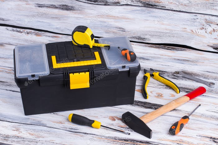 Plumber hand tool kit on wooden background.