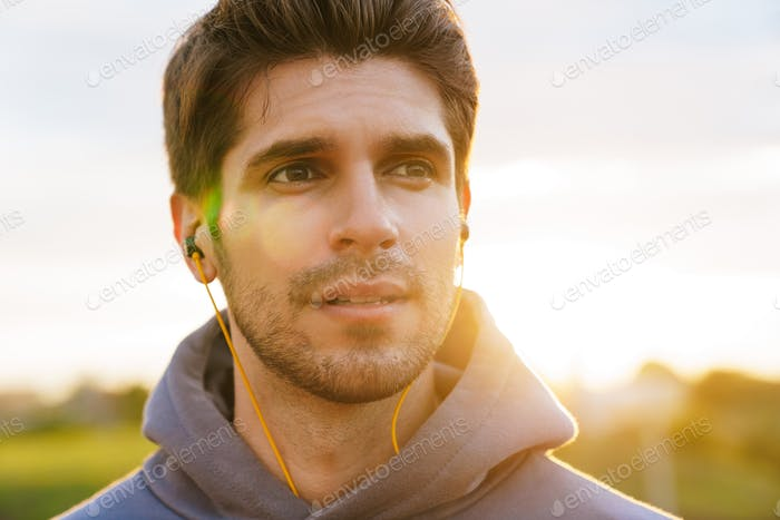 Image of athletic bristle sportsman using earphones and looking aside