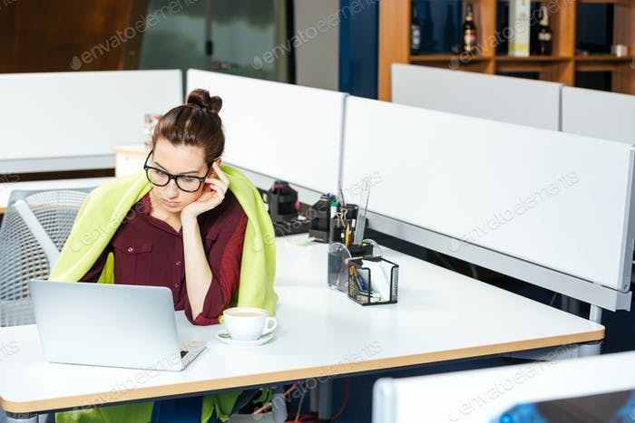 Businesswoman working with laptop and feeling cold in office