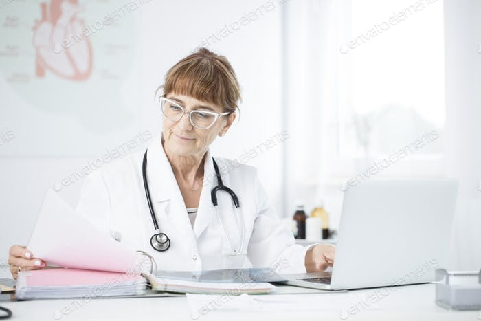 Smiling cardiologist working in office