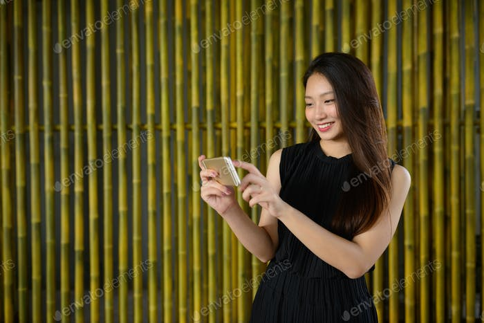 Happy young beautiful Asian businesswoman using phone against bamboo fence