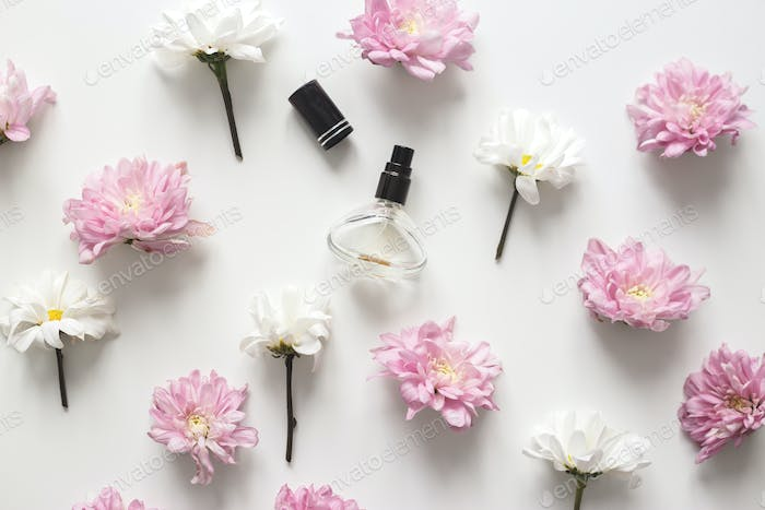 Flat lay composition with spring flowers and perfume jar on white background. Top view, flat lay