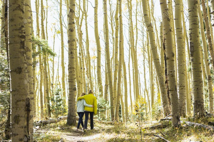 rear view of mother and her teen age daughter hiking in the autumn aspens