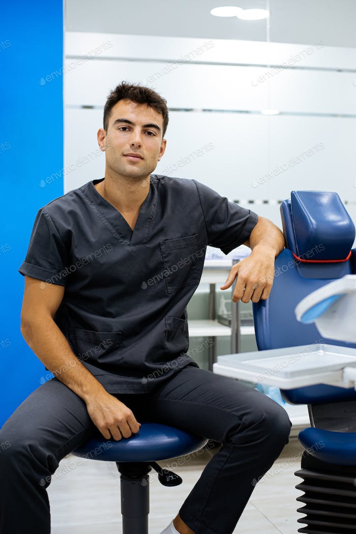 elegant confident man doctor dentist wearing lab coat looking at camera