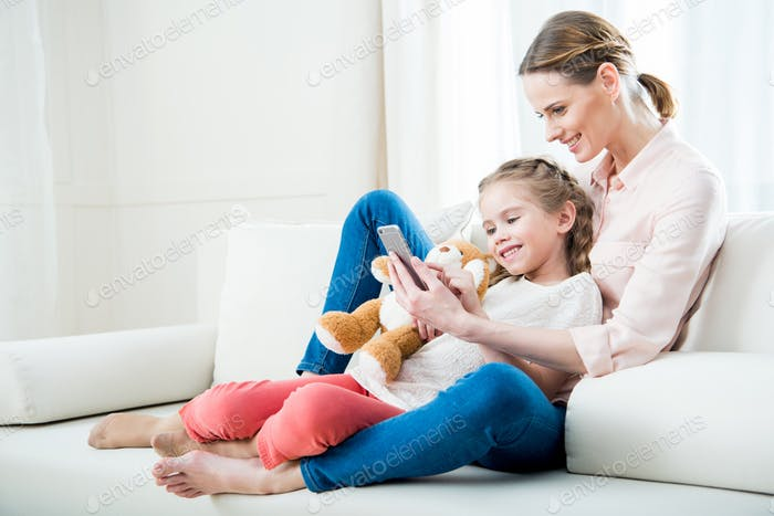 side view of cheerful mother and daughter using smartphone together