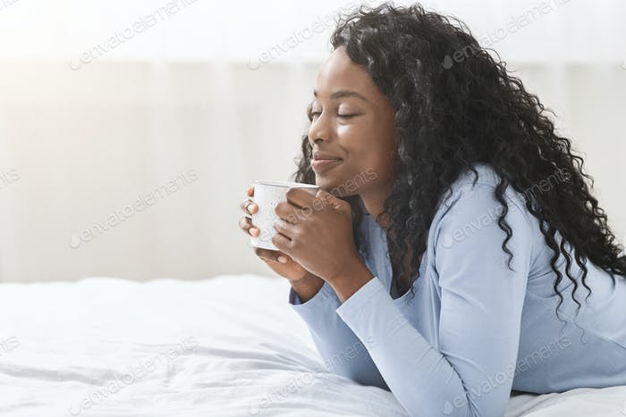 Joyful girl relaxing in bed with cup of coffee