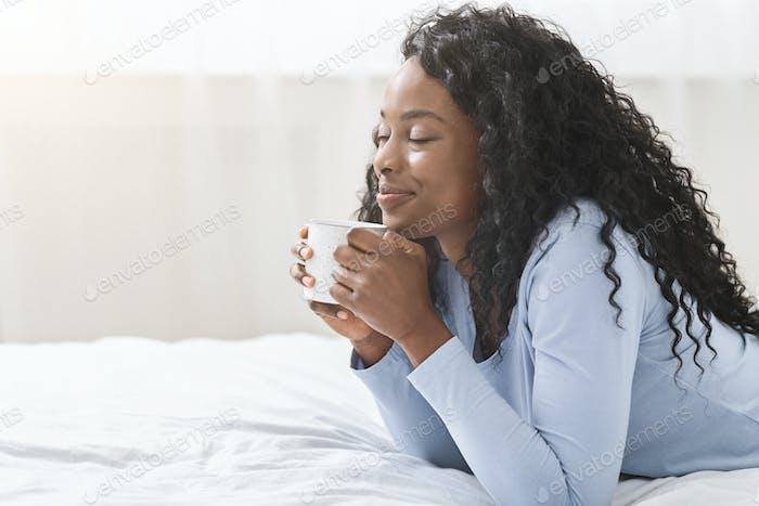 Freudige Mädchen entspannen im Bett mit Tasse Kaffee