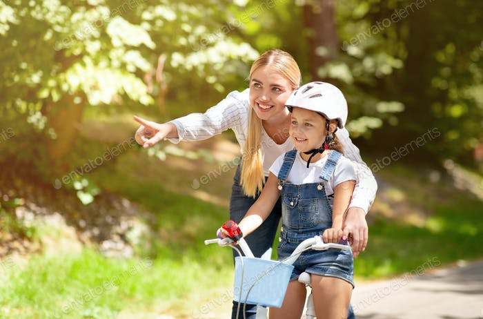 Mom Teaching Daughter To Ride A Bicycle Showing Direction Outside