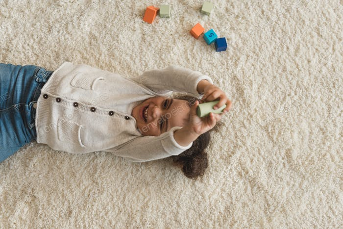 overhead view of happy little girl playing with cubes at home