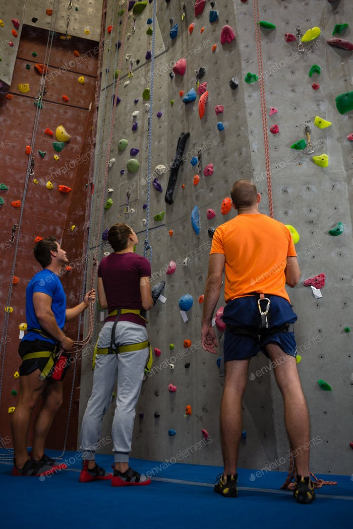 Trainer with athletes standing by climbing wall at gym