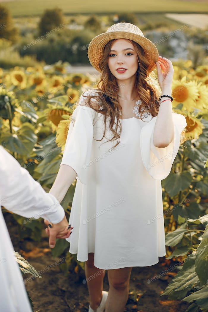 Beautiful and stylish couple in a field wirh sunflowers