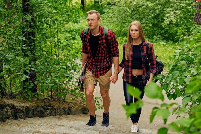 Skateboarder Paar nach oben in Naturparks gehen.
