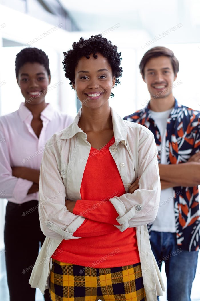 Front view of young diverse business people with arms crossed looking at camera in a modern office