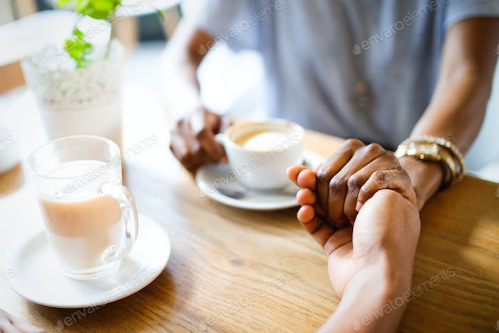 Close-up of couple holding hands while sitting together in cafe with coffee cups on the table