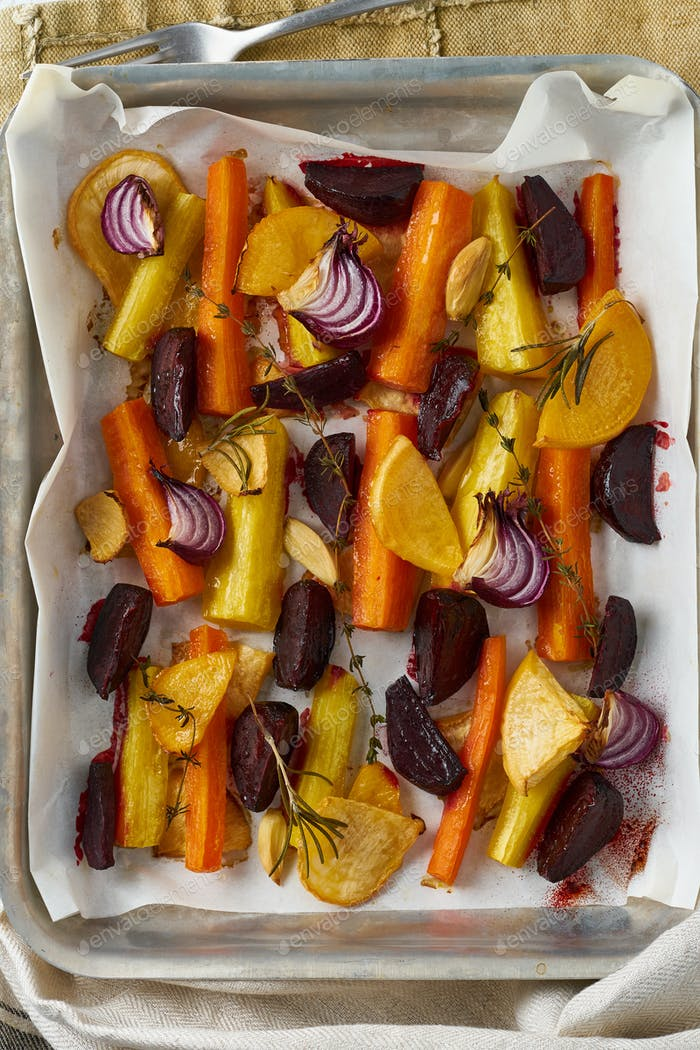 Colorful roasted vegetables on tray with parchment. Mix of carrots, beets, turnips