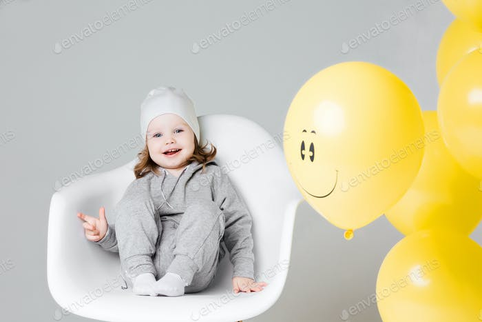 Positive little girl in gray suite with yellow ballon with smile
