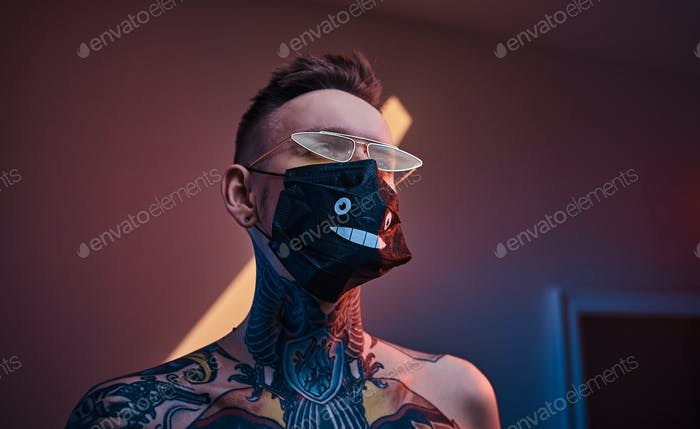 Inked male model posing in a neon studio with half-naked body, sunglasses and medical mask