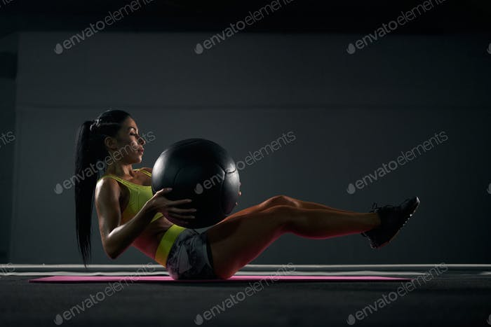 Sportswoman training abs with ball in gym