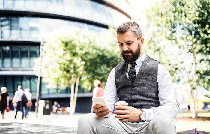 Hipster businessman with coffee and smartphone sitting outdoors in the city.