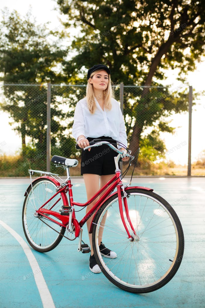 Portrait of thoughtful lady looking in camera while standing with classic bicycle