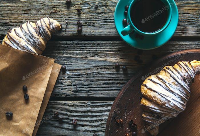 Croissant in einer Papiertüte mit einer Tasse Kaffee. Frühstück, Snack, Essen