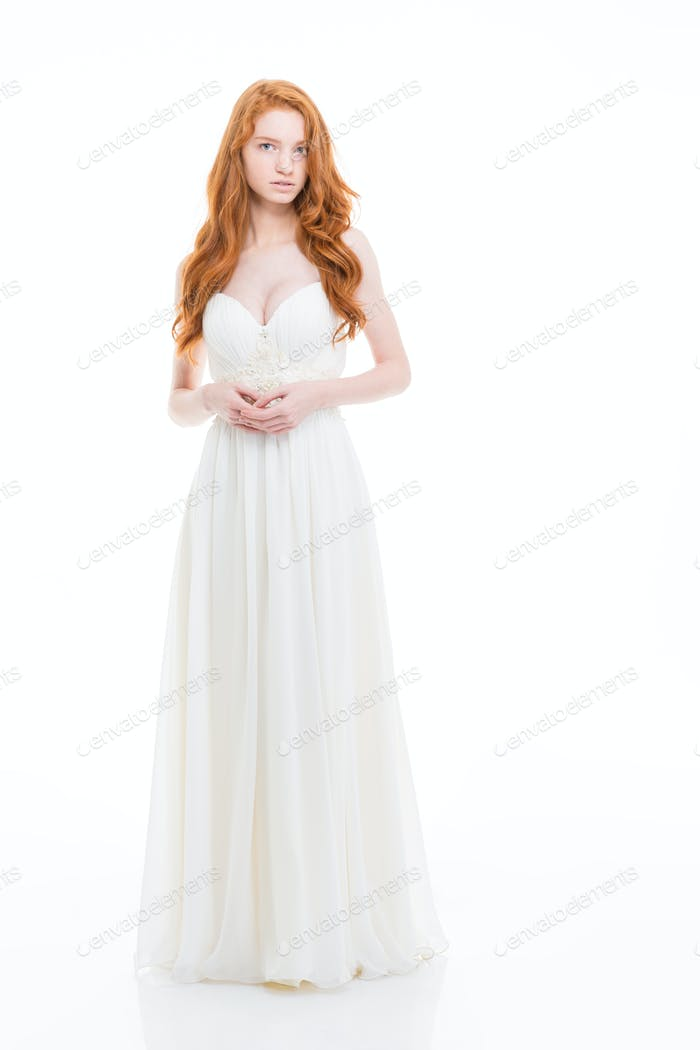 Beautiful young woman with wavy long hair in wedding dress
