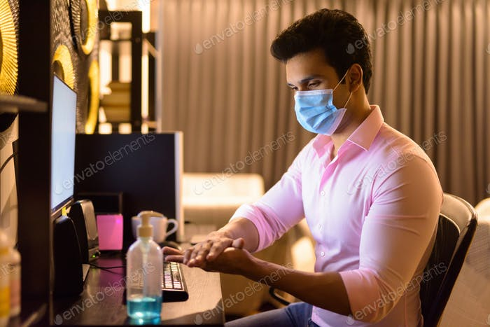 Young Indian businessman with mask using hand sanitizer while working overtime at home during