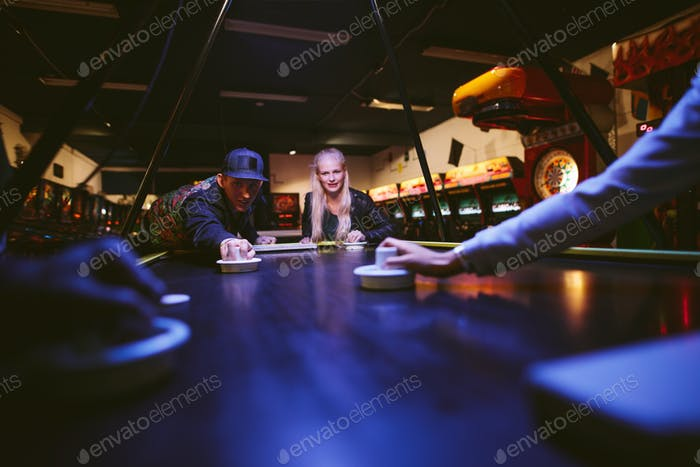 Young man and woman playing air hockey game