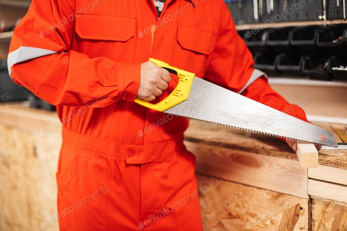 Close up builder in orange work clothes sawing wooden plank with