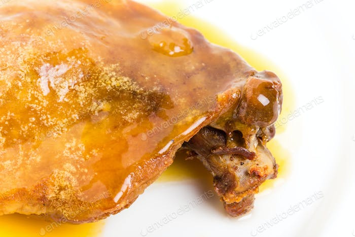 Duck leg confit with yellow sauce.