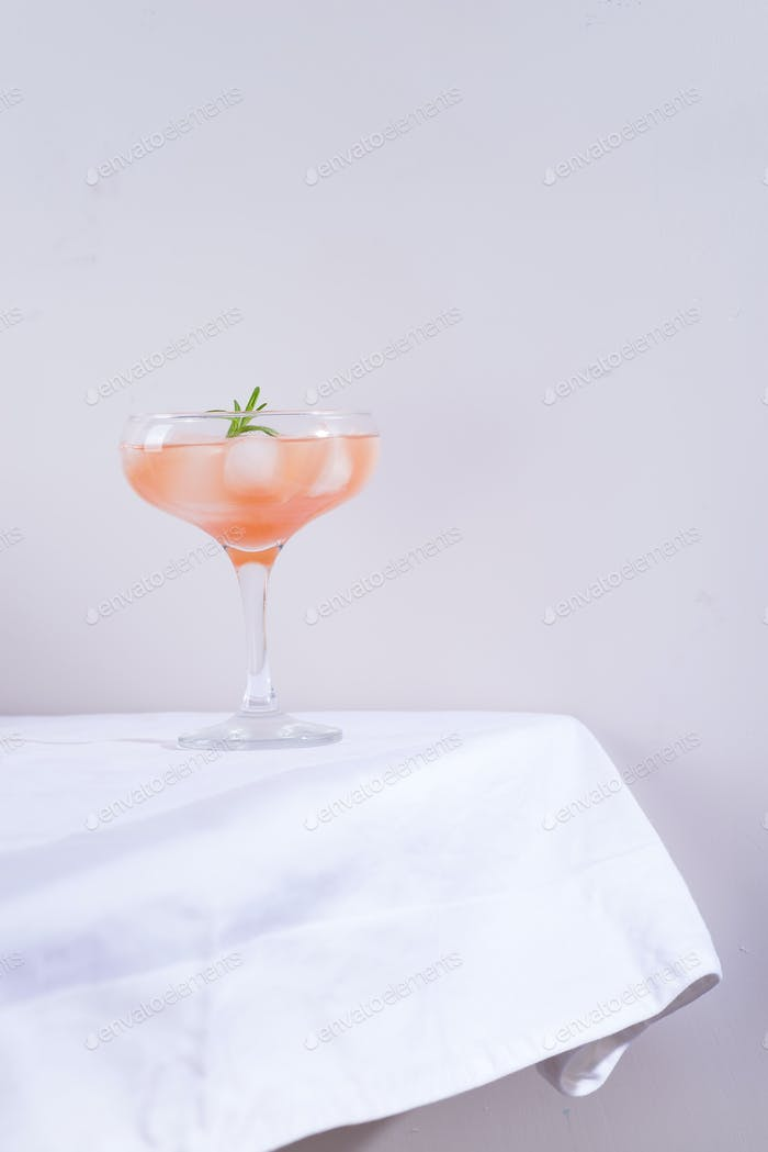 Pink cocktail with rosemary and ice on a white tablecloth on the table