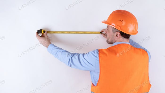 Builder Measuring Wall With Tape-Measure Standing Back To Camera, Studio