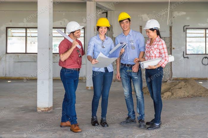 Многоэтнические профессиональные инженеры-строители, работающие с Корпоративный коллегами Team