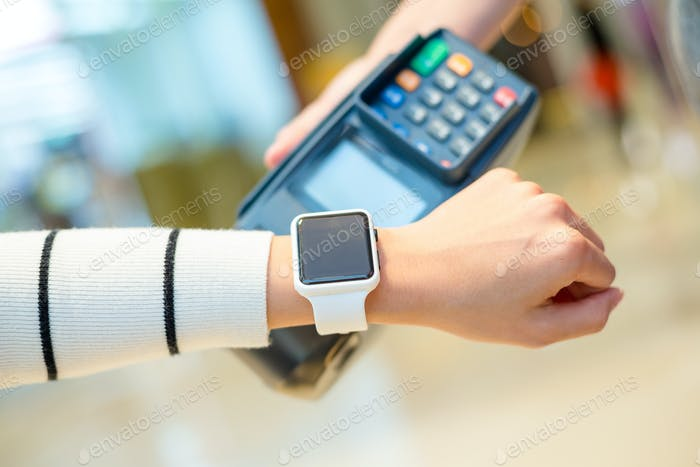 Customer using smartwatch to pay the bill