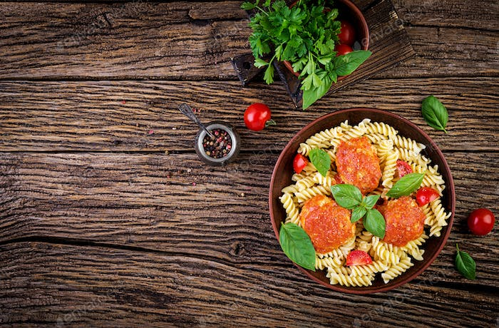 Fusilli  pasta with meatballs in tomato sauce and basil in bowl. Italian cuisine. Top view. Flat lay