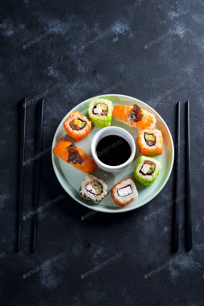 Various Fresh and delicious sushi set on ceramic plate with slate sticks, sauce on black stone