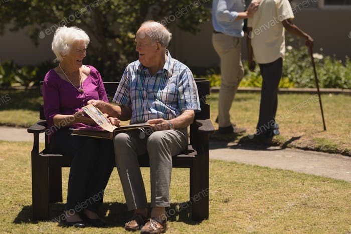 Senior couple laughing and looking at photo album while sitting on a bench in the park