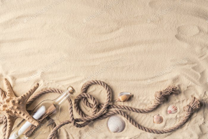 Bottle with letter and shells with rope on light sand