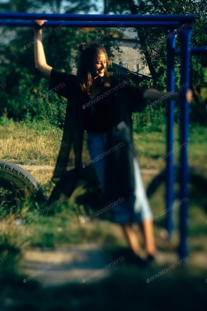 Stylish hipster girl having fun at playground in sunny street