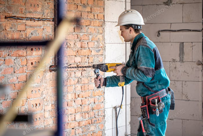 The builder works with a drill in working form.