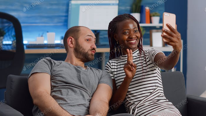 Cheerful interracial couple taking pictures with smartphone